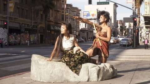 At the corner of a city intersection, two Filipinx femmes with medium brown skin and dark brown hair look off into the distance. One points in the same direction with kali sticks, wearing a red-gold malong. In front of her, the other sits on a large rock, wearing a white top and green floral pants.