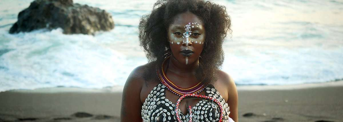 An African American woman with dark brown skin and shoulder-length black curls stands in front of the ocean, wearing a cowrie shell top, white face markings, and gemstones around her eyes.