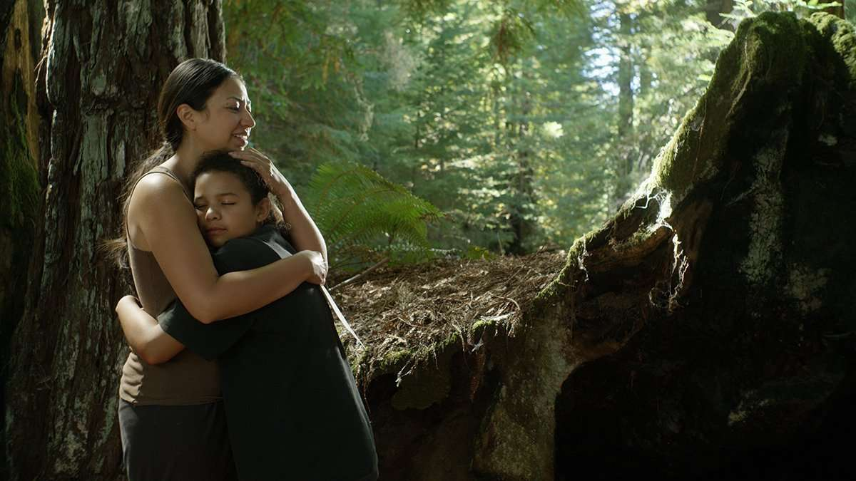 An Indigenous Latina woman and a Black Latina girl smile and hug each other tightly with their eyes closed. They are standing in a forest, with ferns and tall trees behind them.