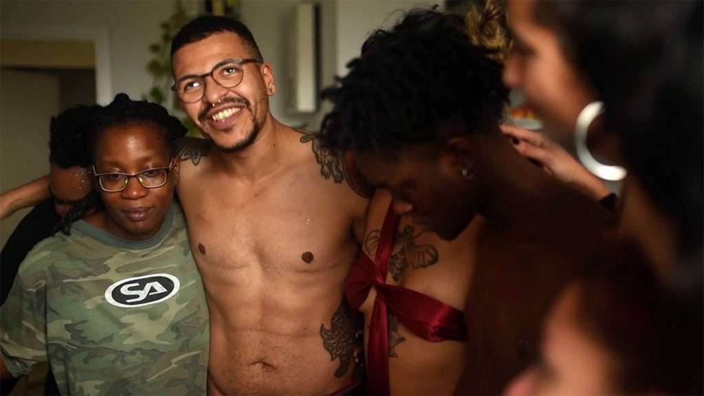 A group of queer people of color stand with their arms around each other. From left to right: a person with dark brown skin, glasses, and a green camo shirt; a shirtless transgender man with medium brown skin, top surgery scars, tattoos, glasses and a nose ring; a person with medium brown skin and tattoos wearing a red satin bra top; a person with dark brown skin and short black hair; a person with medium brown skin, long dark hair, and silver hoop earrings.