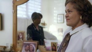 An older white Latina with light brown skin and shoulder-length curly brown hair gazes across the room. Reflected in the dresser mirror behind her is an older Black Latina with dark brown skin and short gray hair, wearing a black dress. On a dresser is an illustration of Jesus and a framed wedding photo with a man and woman.