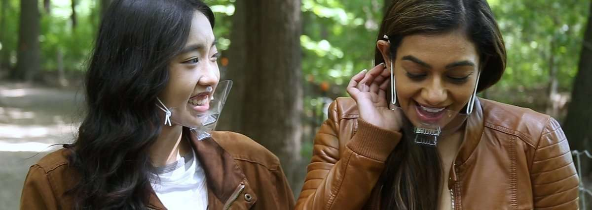 A Vietnamese woman with light skin and long black hair smiles at an Indian woman with medium with medium brown skin who is tucking her long brown hair behind her ear. Both women wear clear plastic face masks while walking amidst verdant green trees.
