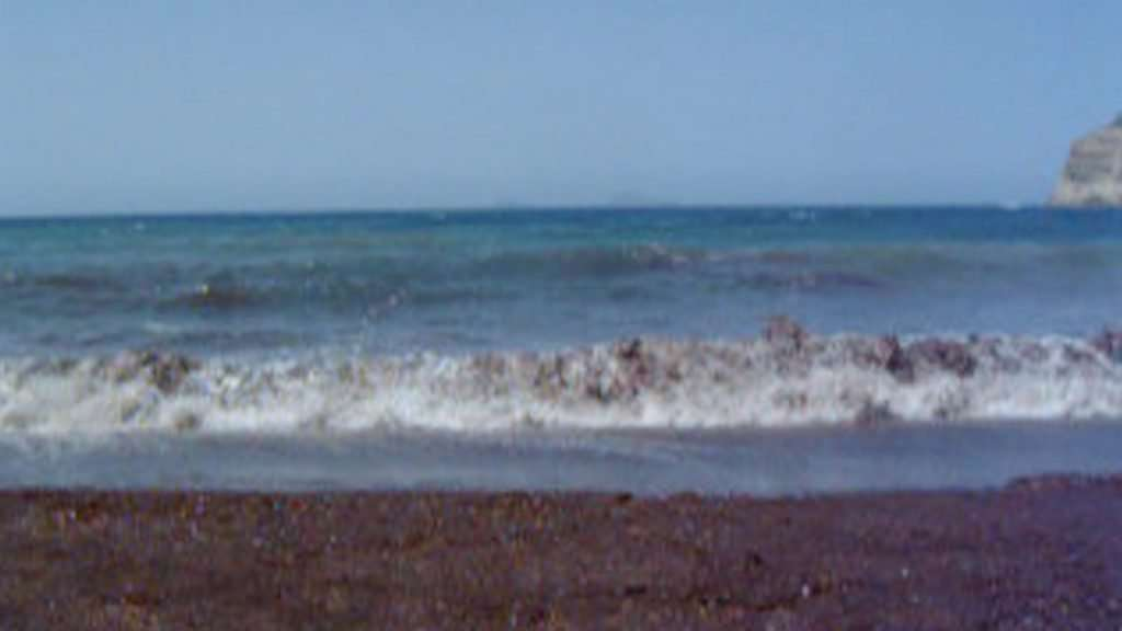 A blurry and pixelated image of a clear blue sky and the ocean, with turquoise swells and waves crashing on a reddish-brown sandy beach. On the right is the edge of a grey cliff.
