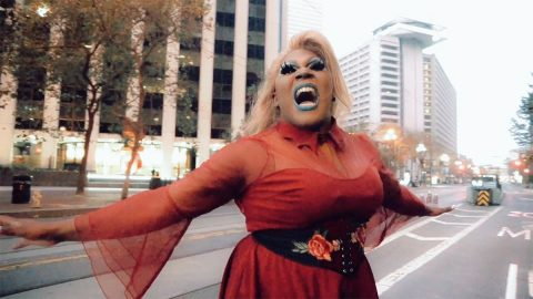 A Black drag queen with dark brown skin and a long blonde wig, singing in a red dress with her arms wide open in the middle of Market Street in San Francisco. Behind her are skyscrapers and streetlights.