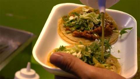 Close up of two tacos in a white styrofoam tray held in one hand in front of a green background, while green sauce is poured onto the tacos.