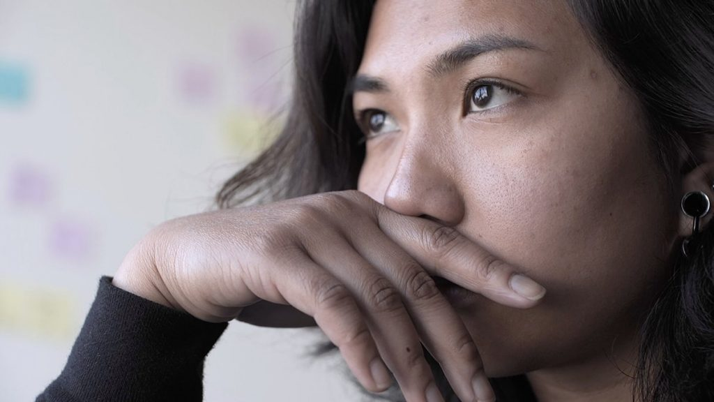A genderfluid Pilipinx person with medium brown skin and wavy brown hair looks off into the distance and leans on their hand, which rests against their mouth. Behind them is a white wall with multicolored post-it notes.